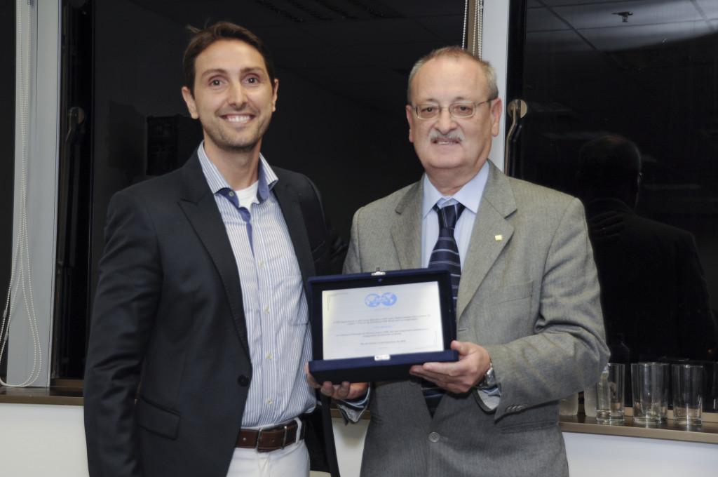 Bruno Moczydlower entrega placa de premiação a Celso Branco.
