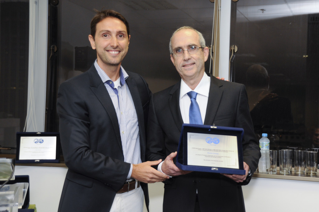 Bruno Moczydlower entrega placa de premiação a Ricardo Camargo.
