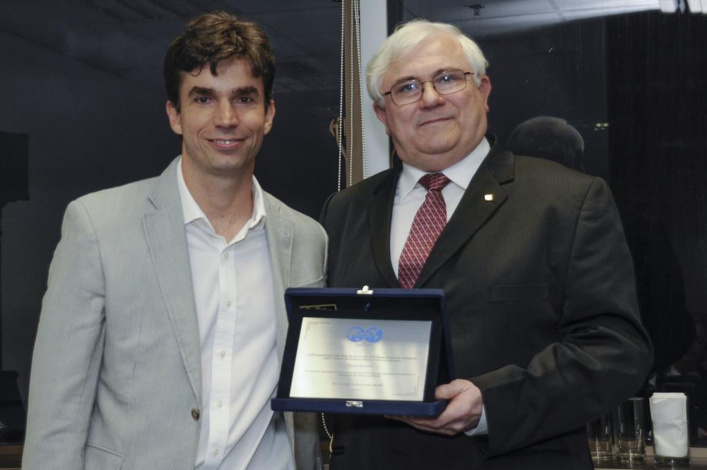 Luiz Otávio Schmall entrega placa de premiação a Daniel Miranda.