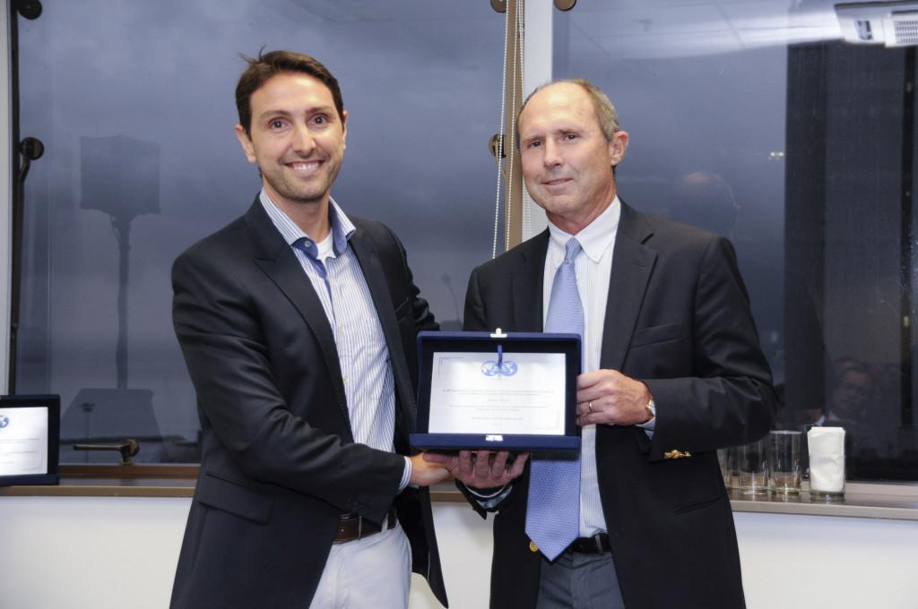 Bruno Moczydlower entrega placa de premiação a Austin Boyd.