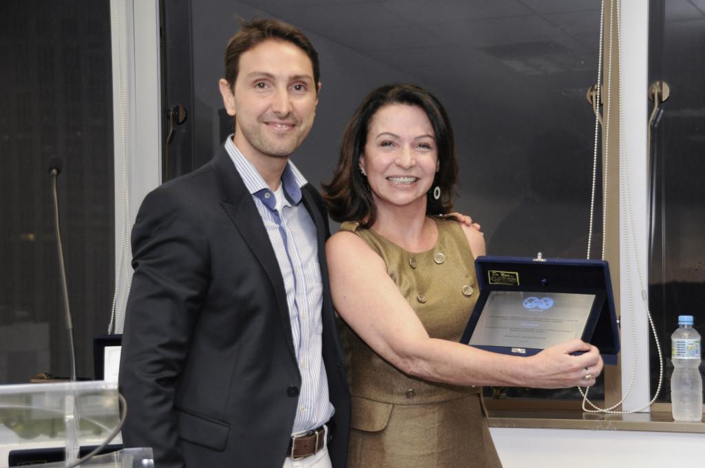 Bruno Moczydlower entrega placa de premiação a Ana Teixeira