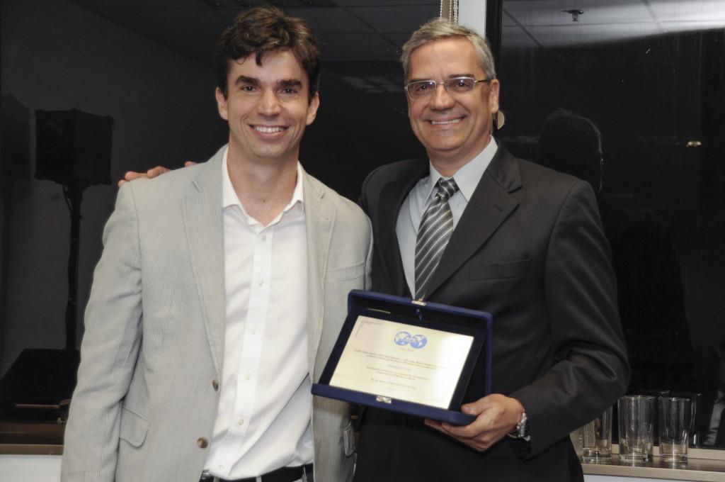 Luiz Otávio Schmall entrega placa de premiação a Waldemar Celes